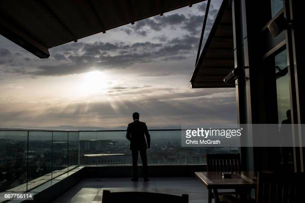 A man smokes at a rooftop bar overlooking the city on April 12 2017 in Malatya Turkey Campaigning by both the 'Evet' and 'Hayir' camps has...