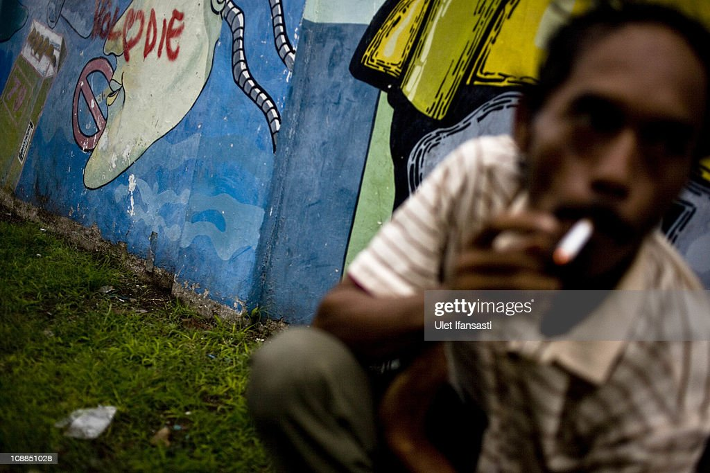 A man smokes infront of graffiti anti-smoking on January 25, 2011 in Yogyakarta, Indonesia. It is estimated that over 25 percent of children in Indonesia over the age of three have tried smoking, with over three percent of them smoking regularly. The lack of government regulation around advertising is blamed for the problem, with campaigns seen heavily at sporting events, music concerts. The Indonesian government previously passed a health bill in 2009 to address the issues, but it has not yet been implemented.