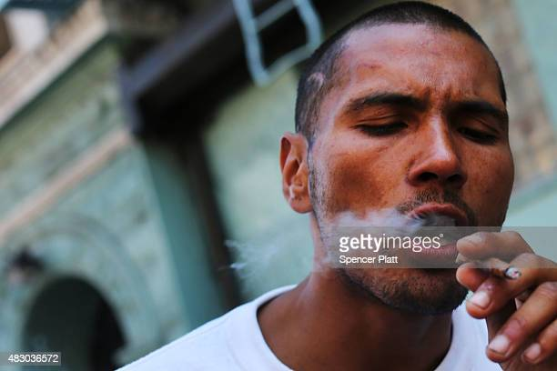 A man smokes K2 or 'Spice' a synthetic marijuana drug along a street in East Harlem on August 5 2015 in New York City New York along with other...