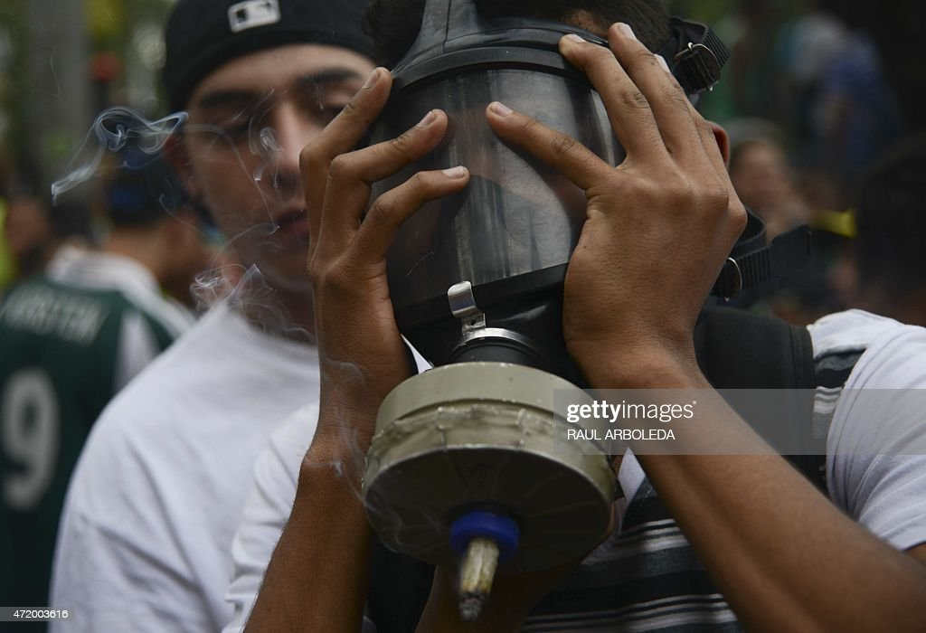 A man smokes marijuana during a demo for its legalization, in Medellin, Antioquia department, Colombia on May 2, 2015. The demo is against drug trafficking and for the self-cultivation for medicinal and recreational purposes. AFP PHOTO/Raul ARBOLEDA