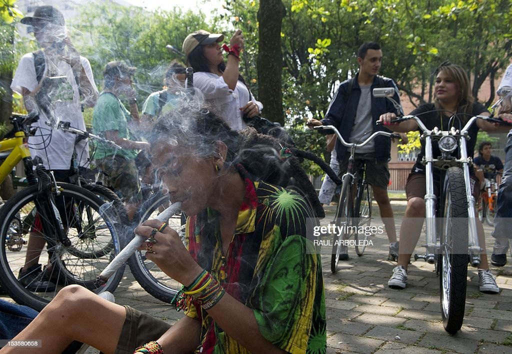 A man smokes marijuana during the first world bicycle ride against drug trafficking and in favour of the legalization of self-cultivation of marijuana for medicinal and recreational purposes in Medellin, Antioquia department, Colombia on October 6, 2012. AFP PHOTO/Raul ARBOLEDA