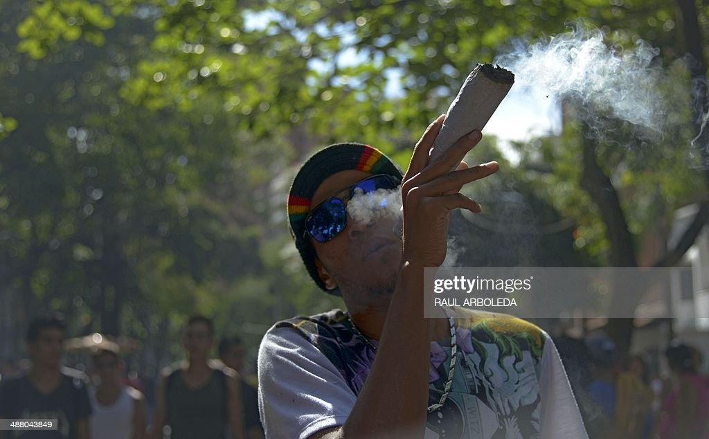 A man smokes marijuana during the World Day for the Legalization of Marijuana in Medellin, Antioquia department, Colombia on May 3, 2014. AFP PHOTO/Raul ARBOLEDA