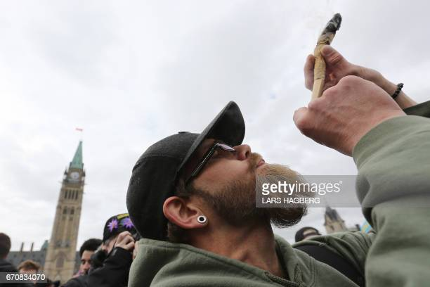 A man smokes marijuana on Parliament Hill on 4/20 in Ottawa Ontario April 20 2017 Polling released Thursday showed strong support in Canada for a...