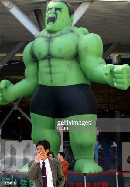 A man smokes next to a giant balloon featuring a character of an American movie 'Hulk' in Shanghai 28 October 2003 US Commerce Secretary Don Evans...
