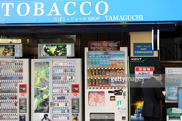 A man smokes next to vending machines in Tokyo Japan on Wednesday Feb 4 2015 Japan Tobacco Inc the maker of Mevius Winston and Camel cigarettes is...