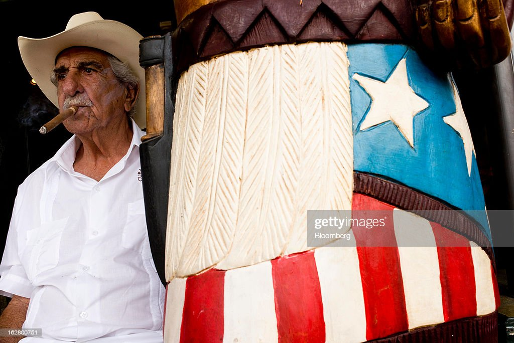A man smokes of a cigar in front of a shop on Calle 8, or Eighth Street, in the Little Havana district of Miami, Florida, U.S., on Wednesday, Feb. 20, 2013. U.S. exports in the travel and tourism sector reached $168.1 billion in 2012, up 10.1 percent from the year-ago level of $152.7 billion, according to data released Feb. 22 by the Commerce Department's International Trade Administration. Photographer: Ty Wright/Bloomberg via Getty Images