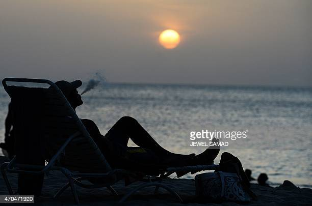 A man smokes on a beach as the sun sets in Saint George's Grenada on April 20 2015 AFP PHOTO/JEWEL SAMAD