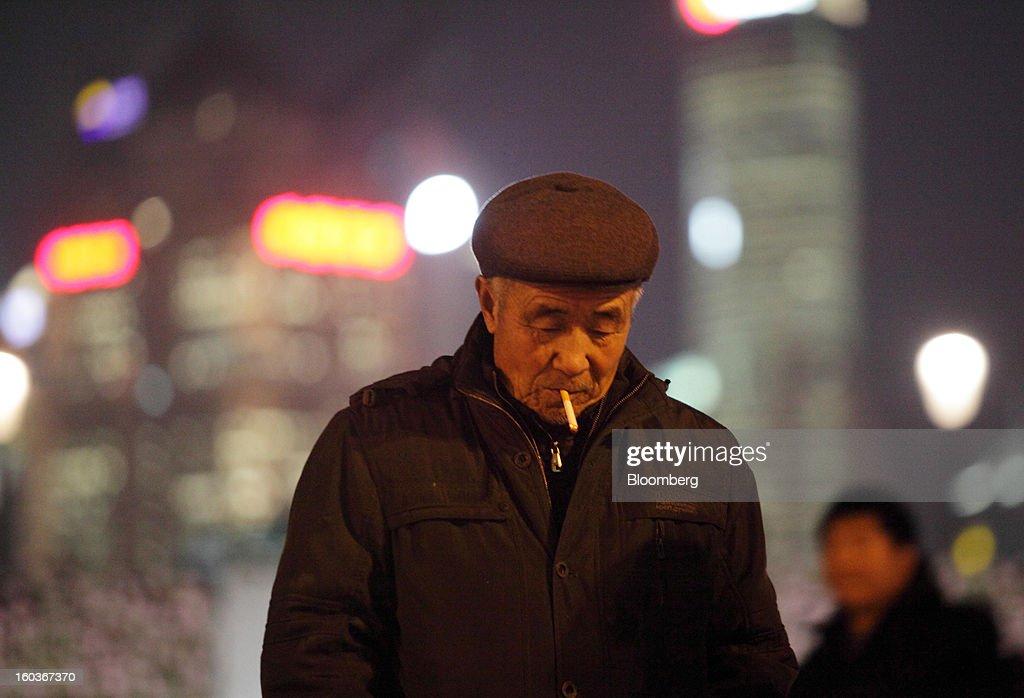 A man smokes on the Bund at night in Shanghai, China, on Monday, Jan. 28, 2013. China's economic growth accelerated for the first time in two years as government efforts to revive demand drove a rebound in industrial output, retail sales and the housing market. Photographer: Tomohiro Ohsumi/Bloomberg via Getty Images