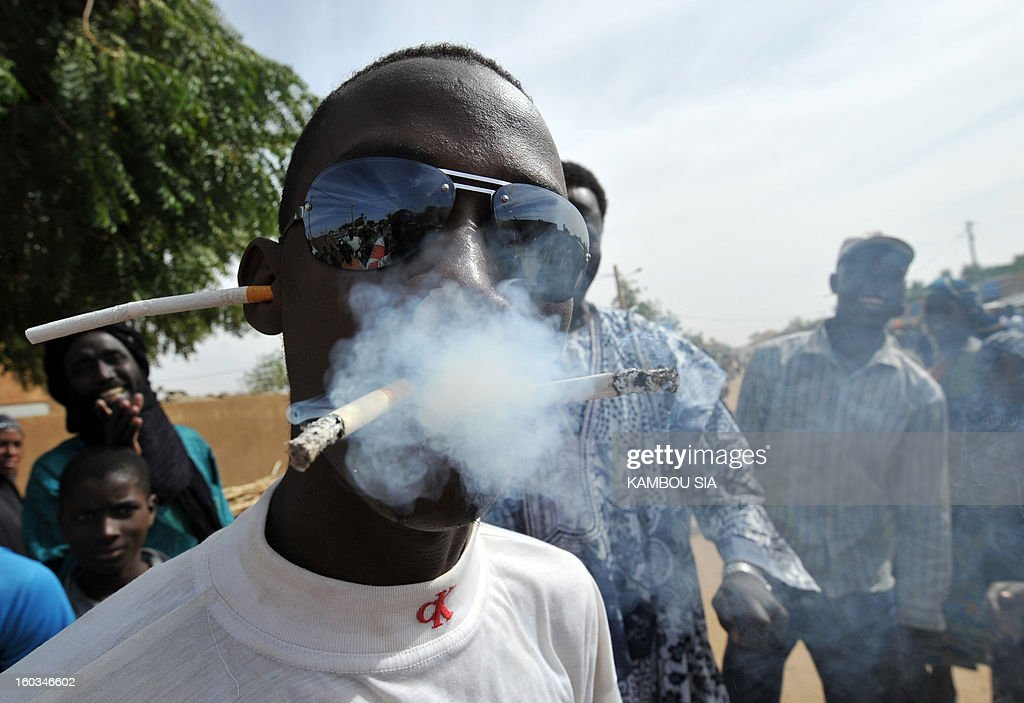 A man smokes several cigarettes to celebrate on January 29, 2013 in Ansongo, a town south of the northern Malian city of Gao, Niger troops entering the city. Troops from Niger and Mali on January 29 entered Ansongo, which along with Gao was recaptured by French-led soldiers over the weekend in a lightning offensive against radicals holding Mali's north. So far, just 2,000 African troops have been sent to Mali or neighboring Niger, many of them from Chad, to boost the French-led offensive which began on January 11 and led to the recapture of several towns, including Ansongo. AFP PHOTO / KAMBOU SIA