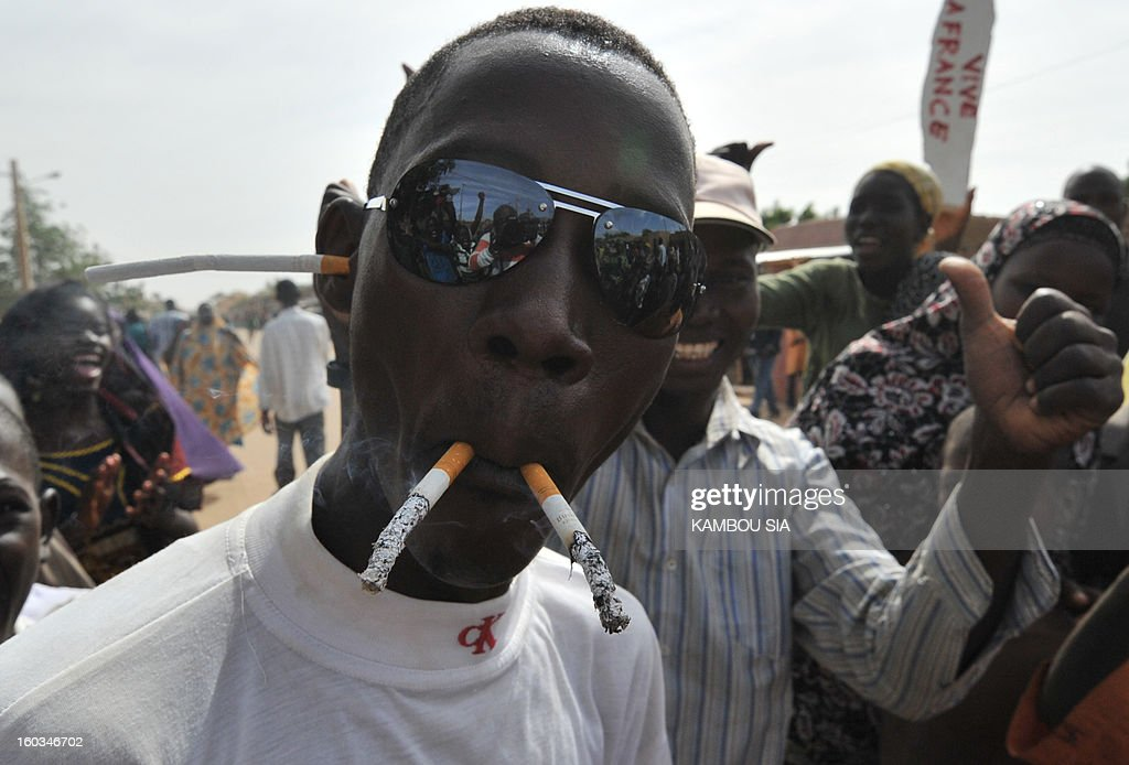 A man smokes several cigarettes to celebrate on January 29, 2013 in Ansongo, a town south of the northern Malian city of Gao, as Niger troops entered the city. Troops from Niger and Mali on January 29 entered Ansongo, which along with Gao was recaptured by French-led soldiers over the weekend in a lightning offensive against radicals holding Mali's north. So far, just 2,000 African troops have been sent to Mali or neighboring Niger, many of them from Chad, to boost the French-led offensive which began on January 11 and led to the recapture of several towns, including Ansongo.
