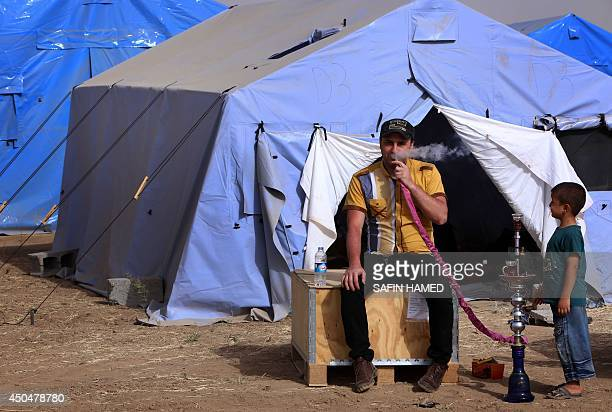 A man smokes water pipe near a boy outside temporary tents set up to shelter Iraqis fleeing violence in Iraq's northern Nineveh province in Aski...
