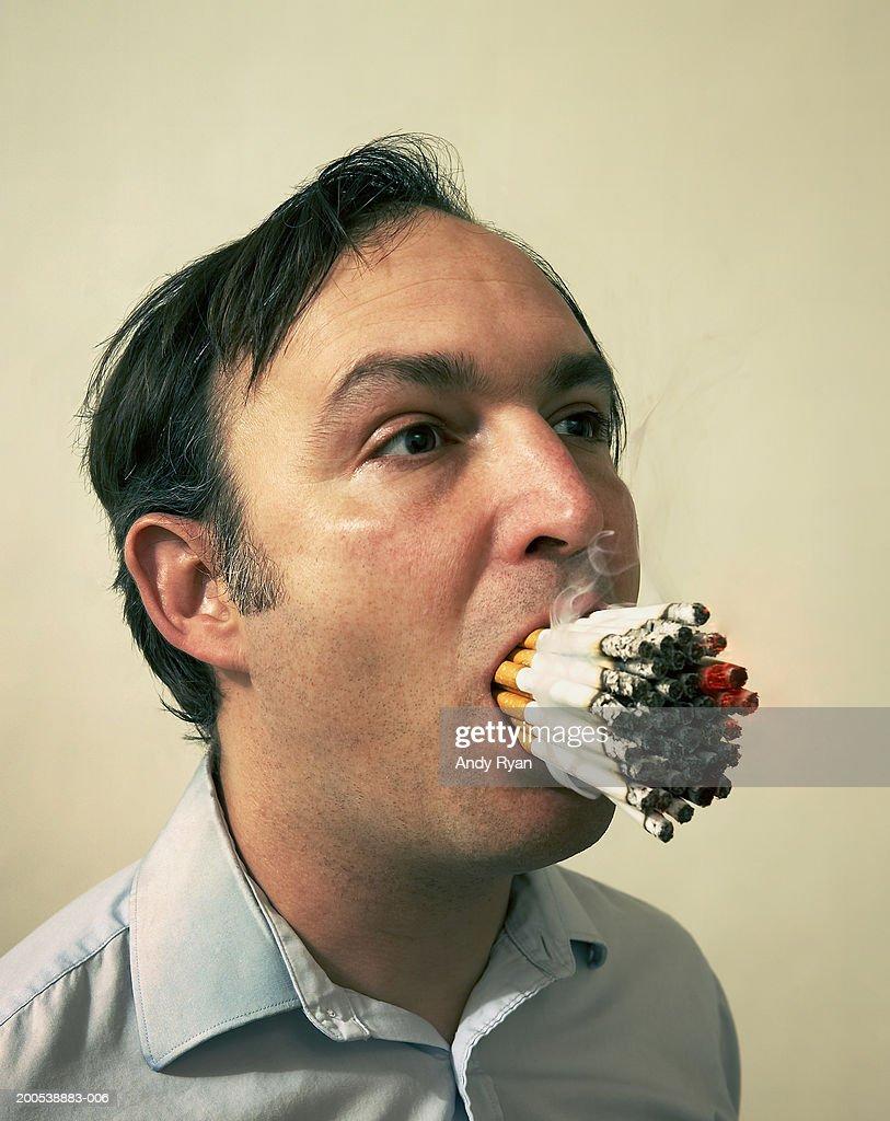 Man smoking 40 cigarettes at once, studio : Stock Photo