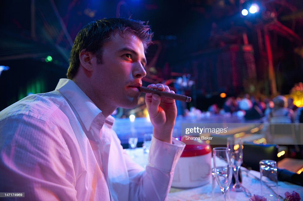 Man smoking a cigar at a night club : Stock Photo