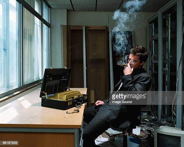Man smoking a cigar with briefcase of gold bars