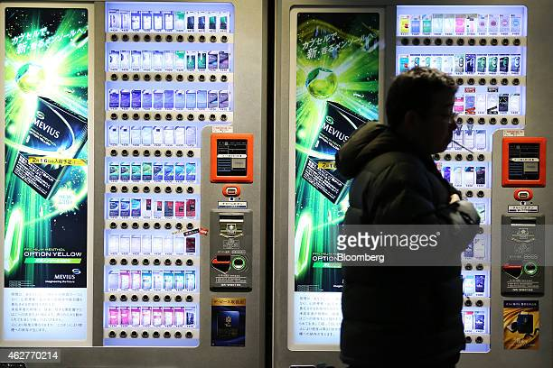 A man smoking a cigarette walks past vending machines in Tokyo Japan on Wednesday Feb 4 2015 Japan Tobacco Inc the maker of Mevius Winston and Camel...