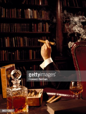 Man smoking cigar in library : Stock Photo