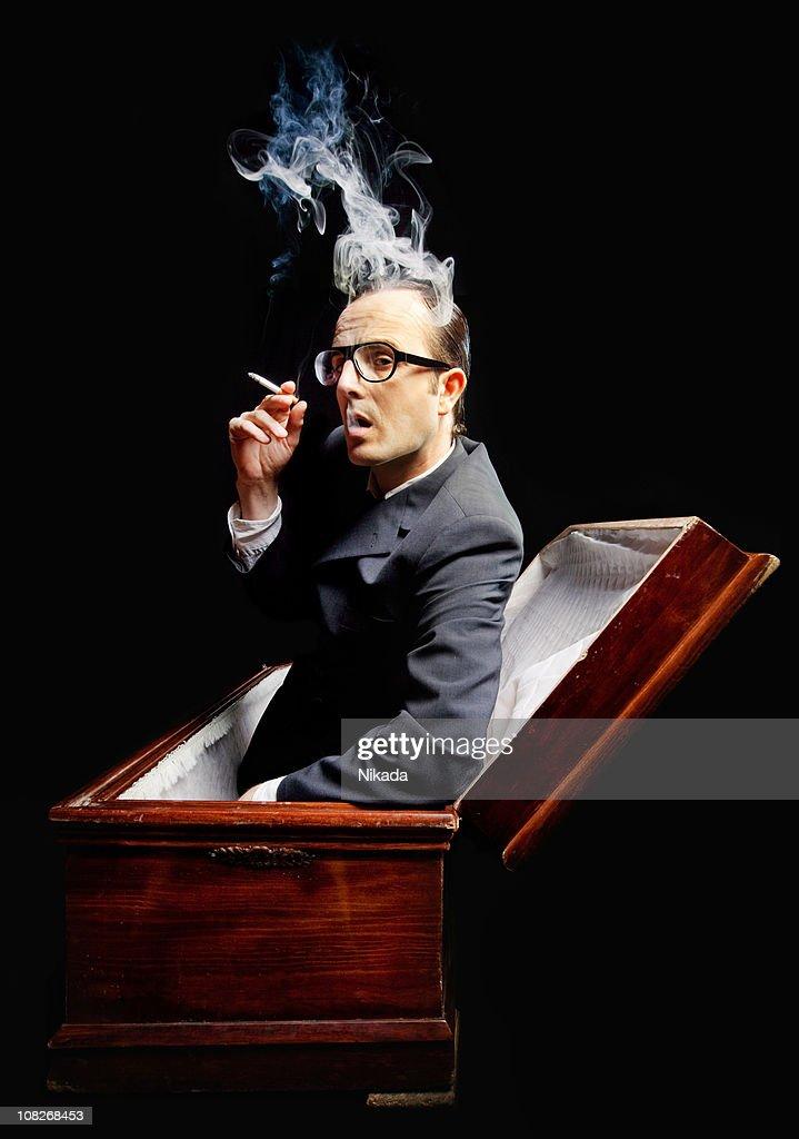 man smoking cigarette in a coffin