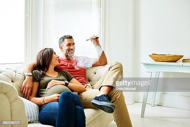 Man smoking electric cigarette with pregnant wife on sofa