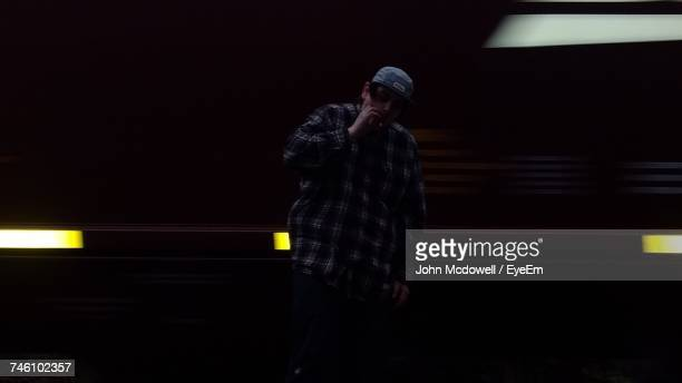 Man Smoking While Standing Against Moving Train During Night
