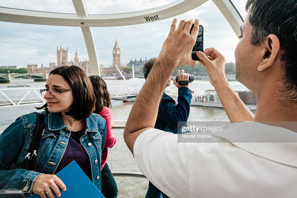 CONTENT] A man snaps a photo of Big Ben with his iPhone as he and his companions enjoy a ride on the London Eye.