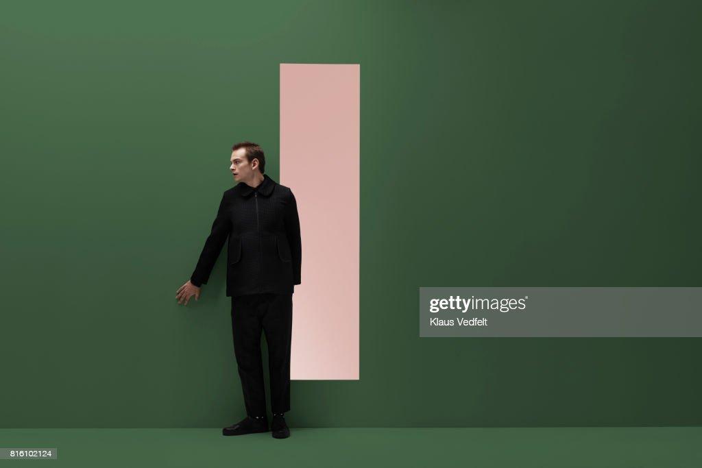 Man sneaks alongside coloured wall in studio : Stock Photo