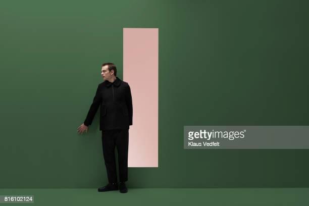 Man sneaks alongside coloured wall in studio