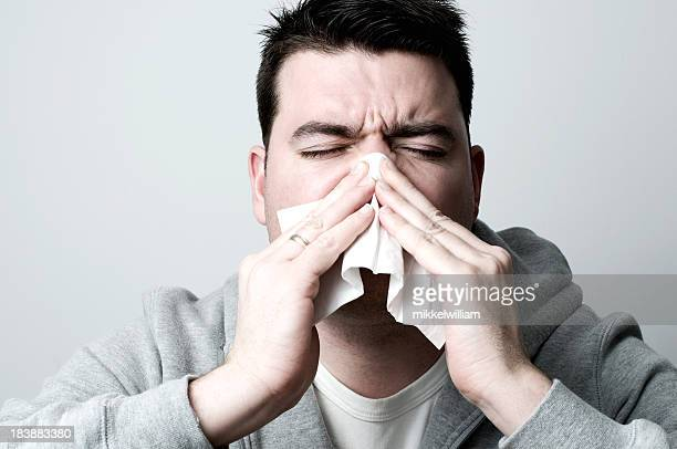 Man sneezing and holding a tissue
