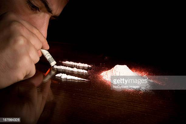 Man sniffing three lines of cocaine