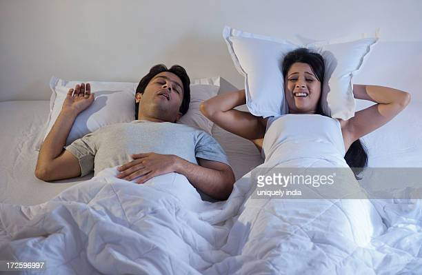 Man snoring with his wife covering ears with pillow on the bed