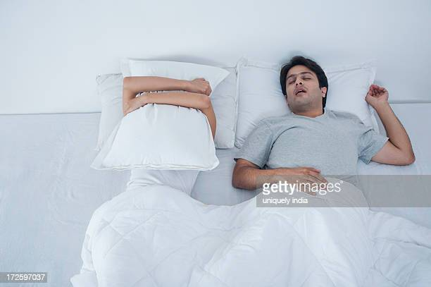 Man snoring with his wife covering her face with pillow on bed