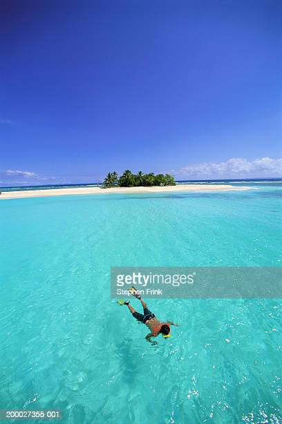 Man snorkeling in Carribean sea off of deserted island, elevated view