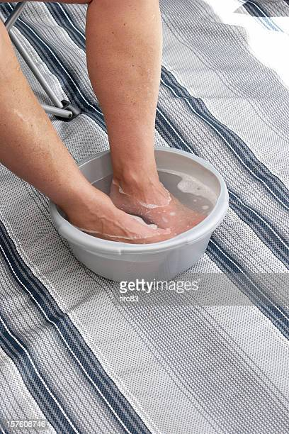 Man soaking feet in bowl of hot water