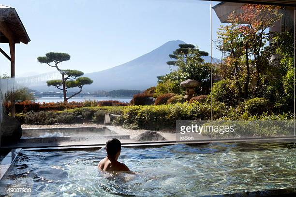 Man soaking in an indoor hot spring pool