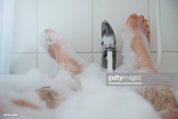 Man soaking in bubble bath, low section