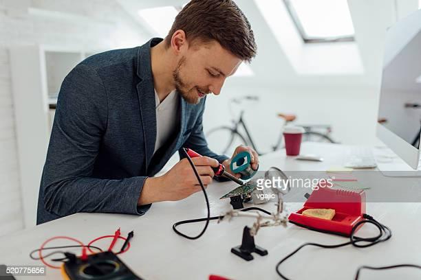 Mann Weichlöten ein Schaltkreis in seinem Büro.