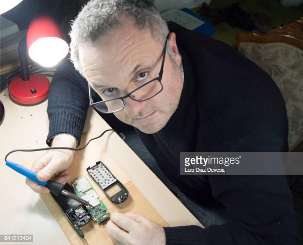 man soldering phone