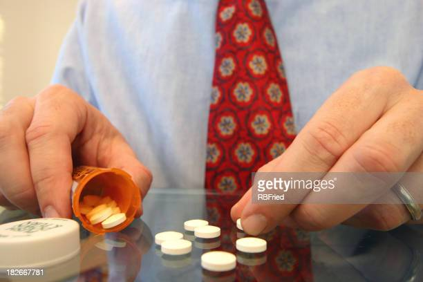 Man sorting his depression medication on glass table