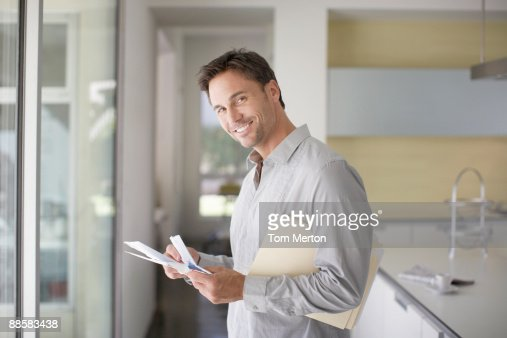 Man sorting mail at home : Stock Photo