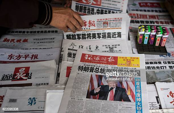 A man sorts Chinese newspapers featuring Donald Trump's victory in the US presidential elections on the front page in Shanghai on November 10 2016...