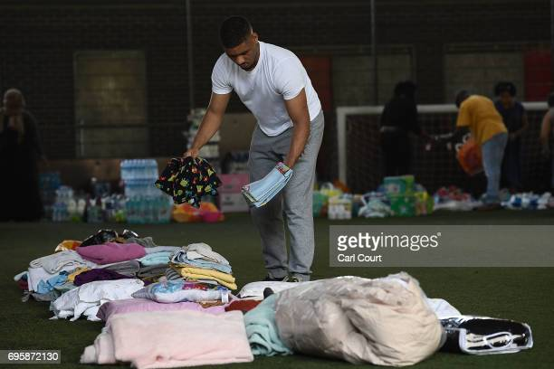 A man sorts out donated clothes in a centre which has been set up to help people near the burning 24 storey residential Grenfell Tower block in...