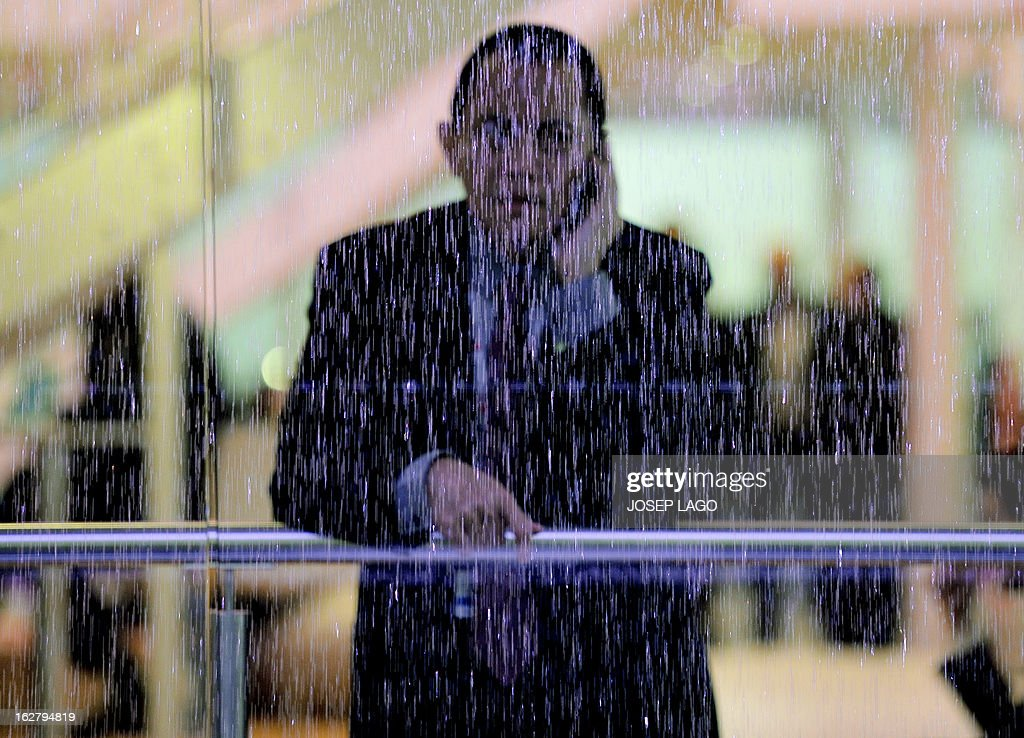 A man speaking on his phone looks through a window pane as it rains in Barcelona on February 27, 2013, on the third day of the 2013 Mobile World Congress. The 2013 Mobile World Congress, the world's biggest mobile fair, is held from February 25 to 28 in Barcelona.