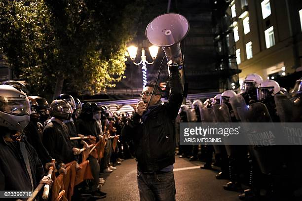 TOPSHOT A man speaks into a megaphone as demonstrators hold red flags during a protest against the visit of the US president in Athens on November 15...