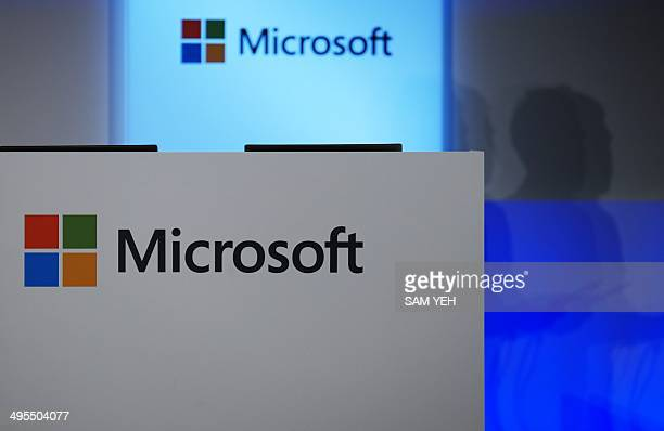 A man speaks next to the Microsoft logos during the Computex tech show in Taipei on June 4 2014 More than 1500 exhibitors including some of the...