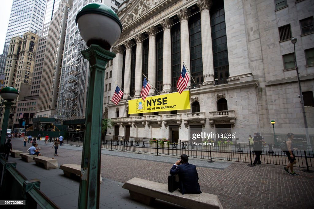 A man speaks on a mobile device outside of the New York Stock Exchange (NYSE) in New York, U.S., on Monday, June 19, 2016. U.S. stocks rose, following a lull in markets after equities hit another fresh record last week. Photographer: Michael Nagle/Bloomberg via Getty Images