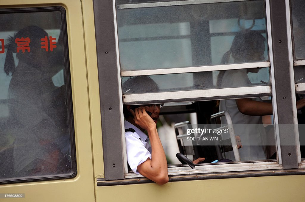 A man speaks on a mobile phone as he sit on a bus in downtown Yangon on August 16, 2013. Qatar's Ooredoo, winner of one of two telecom licenses for Myanmar, introduced during a press conference its plans for one of the world's last virtually untapped mobile phone markets. AFP PHOTO/ Soe Than WIN