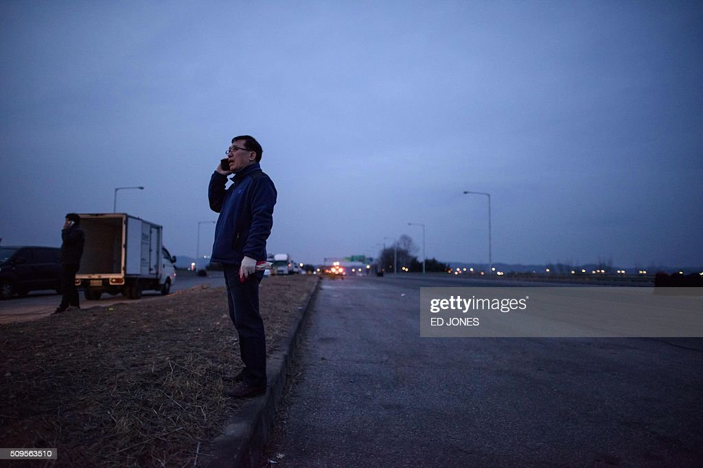 A man speaks on a mobile phone as he stands beside vehicles parked on a roadside which were returning from the Kaesong joint industrial area near a checkpoint of the Demilitarized Zone (DMZ) separating North and South Korea, in Paju on February 11, 2016. North Korea on February 11 expelled all South Koreans from the jointly-run Kaesong industrial zone and seized their factory assets, saying Seoul's earlier decision to shutter the complex had amounted to a 'declaration of war'. AFP PHOTO / Ed Jones / AFP / ED JONES