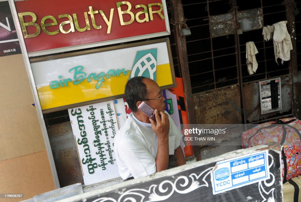 A man speaks on a mobile phone in downtown Yangon on August 16, 2013. Qatar's Ooredoo, winner of one of two telecom licenses for Myanmar, introduced during a press conference its plans for one of the world's last virtually untapped mobile phone markets. AFP PHOTO/ Soe Than WIN