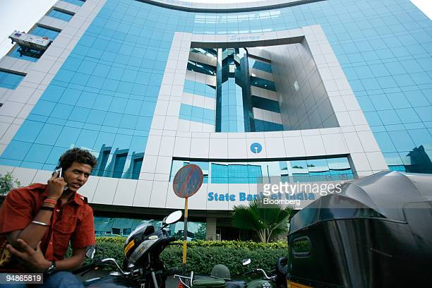 A man speaks on a mobile phone outside the State Bank of India building in Mumbai India on Monday Oct 27 2008 State Bank of India the nation's...