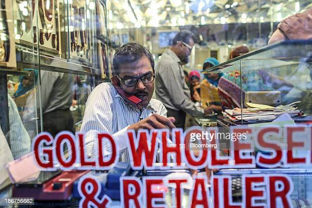 A man speaks on a phone inside a gold jewelry and bullion store during the festival of Dhanteras two days before Diwali in the Zaveri Bazaar area of...