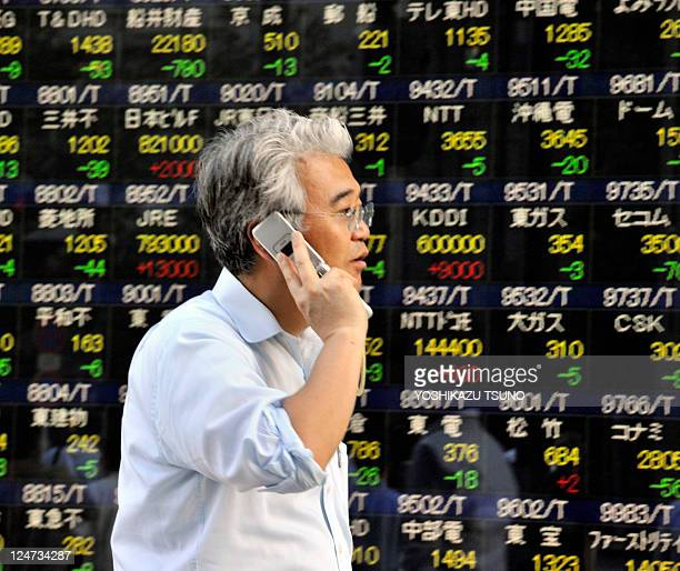 A man speaks on his mobile phone as he walks past a stock market index price board in Tokyo on September 12 2011 Japan's share prices fell 20199...